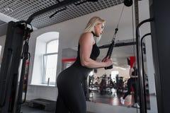 A jovem mulher no sportswear preto está fazendo exercícios da força para as mãos no gym moderno A menina vai dentro para esportes imagens de stock royalty free
