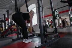 Jovem mulher no sportswear preto na grande forma que faz exercícios com um fingerboard do metal em um gym moderno imagem de stock