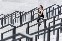 Jovem mulher no sportswear que movimenta-se em escadas do estádio foto de stock royalty free