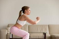 Jovem mulher no sportswear que squatting em casa foto de stock royalty free
