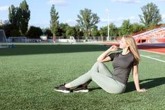 A jovem mulher no sportswear senta-se no campo de futebol fotografia de stock royalty free