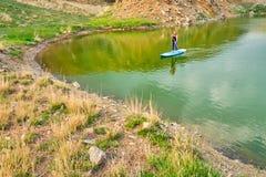 Jovem mulher no SUP da placa de pá no lago Iacobdeal, Romênia, remando perto da linha costeira, em águas tranquilos, pristine, no foto de stock royalty free