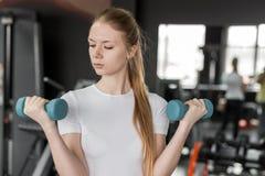 Jovem mulher no t-shirt branco que faz exercícios com pesos azuis no gym Imagem de Stock