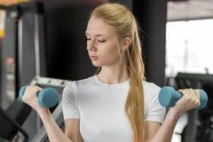 Jovem mulher no t-shirt branco que faz exercícios com pesos azuis no gym Imagem de Stock Royalty Free