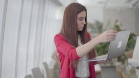 Jovem mulher no terno vermelho que datilografa em seu dispositivo no escritório claro moderno A menina fecha seus netbook e sorri filme