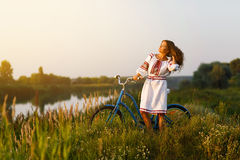 Jovem mulher no traje popular ucraniano nacional com bicicleta Fotos de Stock Royalty Free
