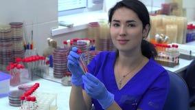 Jovem mulher no uniforme azul que toma dois tubos de uma cremalheira para os tubos de ensaio e que verifica a cor e a consist?nci vídeos de arquivo