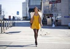 Jovem mulher no vestido amarelo que cruza a estrada fora foto de stock