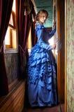 Jovem mulher no vestido azul do vintage que está no corredor de retro fotografia de stock royalty free