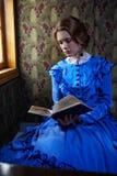 Jovem mulher no vestido azul do vintage que lê o livro no cupê de r fotos de stock royalty free