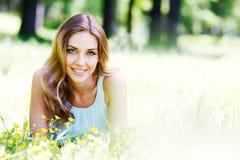 Jovem mulher no vestido azul que encontra-se na grama Imagem de Stock