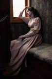 Jovem mulher no vestido bege do vintage do sleapin do início do século XX fotografia de stock royalty free