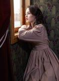 Jovem mulher no vestido bege do vintage que olha a calha a janela dentro Imagem de Stock