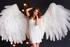 Jovem mulher no vestido branco com asas do anjo fotos de stock