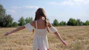 A jovem mulher no vestido branco com cabelo da trança gerencie no fundo da paisagem do estepe no dia claro filme