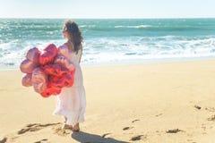 Jovem mulher no vestido branco que guarda balões vermelhos na praia Imagens de Stock Royalty Free