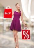 Jovem mulher no vestido com sacos de compras vermelhos Foto de Stock
