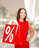 Jovem mulher no vestido com sacos de compras vermelhos Fotos de Stock