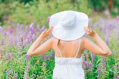 Jovem mulher no vestido e no chapéu brancos no campo Fotos de Stock Royalty Free