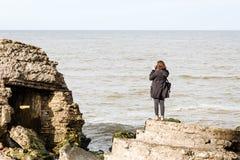 Jovem mulher no vestido escuro que aprecia a praia Fotos de Stock Royalty Free