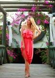 Jovem mulher no vestido no jardim de florescência da flor na ponte de madeira Fotografia de Stock