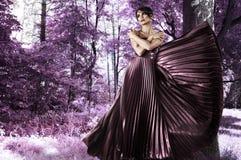 Jovem mulher no vestido longo na floresta Imagem de Stock