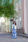 Jovem mulher no vestido longo que anda na cidade velha de Tallinn Imagem de Stock