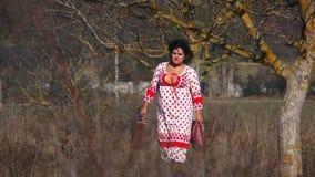 Jovem mulher no vestido pontilhado branco que anda em filme