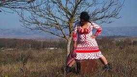 Jovem mulher no vestido pontilhado branco que levanta na natureza video estoque