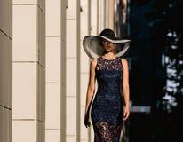 Jovem mulher no vestido preto do laço e em um chapéu com uma borda larga imagens de stock royalty free
