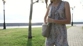 A jovem mulher no vestido retira do telefone esperto da bolsa e começa negociações video estoque