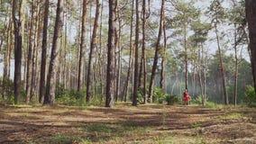 Jovem mulher no vestido vermelho com curva que anda no parque filme
