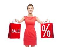 Jovem mulher no vestido vermelho com sacos de compras Fotografia de Stock Royalty Free