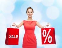 Jovem mulher no vestido vermelho com sacos de compras Imagens de Stock Royalty Free