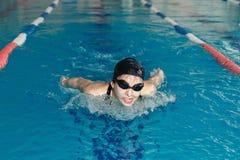 Jovem mulher nos óculos de proteção e estilo do curso de borboleta da natação do tampão na associação interna da raça da água azu fotografia de stock royalty free