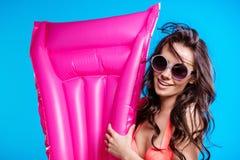 Jovem mulher nos óculos de sol e no biquini que guardam o colchão de ar e que sorriem na câmera imagem de stock royalty free