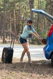 Jovem mulher nos óculos de sol perto do carro com uma mala de viagem Fotografia de Stock Royalty Free