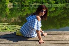 A jovem mulher nos óculos de sol senta-se na ponte perto do rio na foto de stock