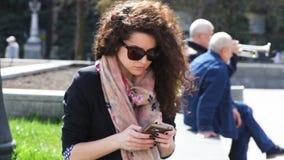 Jovem mulher nos óculos de sol usando o smartphone fora vídeos de arquivo