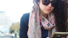 Jovem mulher nos óculos de sol usando o smartphone fora filme
