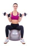 A jovem mulher nos esportes veste o assento na bola da aptidão com peso Imagem de Stock Royalty Free