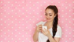 A jovem mulher nos fones de ouvido bebe o batido de fruta com uma palha, de um sorriso e uns olhares na tela de seu smartphone E video estoque