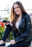 A jovem mulher nos fones de ouvido está sentando-se no parapeito de pedra Imagem de Stock