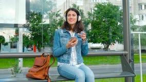 Jovem mulher nos fones de ouvido que aprecia a música, esperando o transporte público ao sentar-se na estação moderna do bonde video estoque