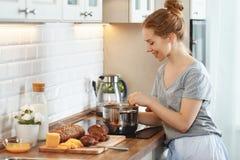 A jovem mulher nos pijamas prepara o café da manhã na manhã foto de stock