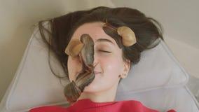 A jovem mulher nos termas recebe uma massagem facial com caracóis Achatina Os caracóis comem a pele inoperante das produzidas Em vídeos de arquivo