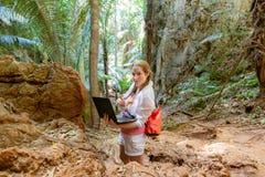 Jovem mulher nos trabalhos brancos com um port?til nas montanhas e na selva tropical Trabalho no curso Olha na c?mera foto de stock