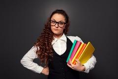 Jovem mulher nos vidros com a pilha dos livros Foto de Stock Royalty Free