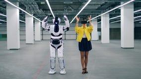 A jovem mulher nos VR-vidros e um robô estão juntando filme