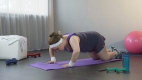 Jovem mulher obeso que levanta e que cai no assoalho, trabalhando duramente para perder o peso video estoque